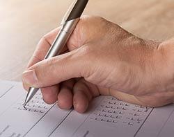 mano con penna che compila questionario